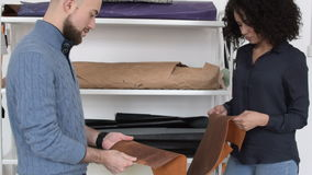 Two clothing designers choosing leather. Standing at stack with samples stock video footage
