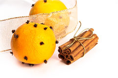 Two cloves-decorated oranges and cinnamon sticks. In the stack with gold ribbon, gold ribbon in the background, white, isolating background Stock Photography