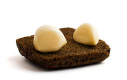Two cloves of garlic on a piece of black bread Royalty Free Stock Images