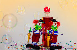 Two clowns with bottle. Two clowns lean on a bottle and are surrounded by bubbles and confetti Stock Photos