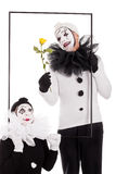 Two clowns in a frame with flower Stock Image