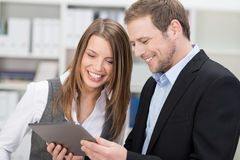 Two co-workers smiling at information on a tablet Royalty Free Stock Images