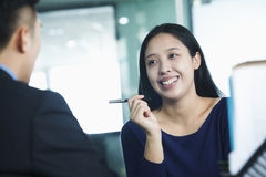 Two co-workers talking in office, holding pen Royalty Free Stock Images