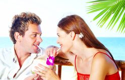 Two and cocktail. A portrait of attractive couple having date on the beach Stock Image