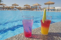 Two cocktail drinks by a tropical swimming pool. Two cocktail drinks by a tropical hotel resort swimming pool in summer Stock Photos