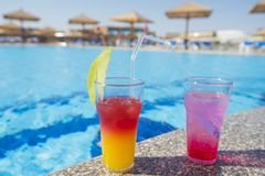 Two cocktail drinks by a tropical swimming pool. Two cocktail drinks by a tropical hotel resort swimming pool in summer Stock Photo