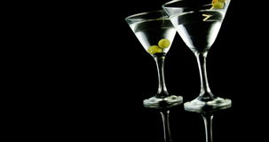 Two cocktail glasses garnished with green olives. Against black background stock video footage
