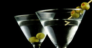 Two cocktail glasses garnished with green olives. Against black background stock video