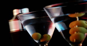 Two cocktail glasses with green olives. Close-up of two cocktail glasses with green olives stock footage