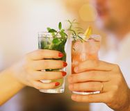 Two cocktail glasses in man and woman hand. Close up Royalty Free Stock Photography