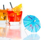 Two cocktail with orange slice on top isolated behind blue umbrella on white background Royalty Free Stock Photography