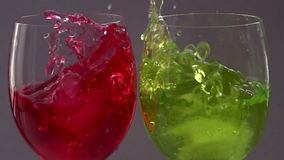 Two cocktails. In beverages falling ice cubes and create a colorful splash stock footage