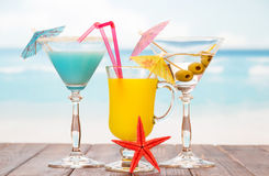 Two cocktails,  glass of juice and starfish on  sea background. Stock Photo