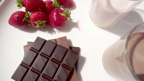 Two cocktails in glasses and a strawberry with chocolate. On white rotate in a circle stock video footage
