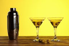 Two cocktails in martini glasses with green olives and shaker on a wooden surface against yellow background with copy space stock image