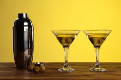 Two cocktails in martini glasses with green olives and shaker on a wooden surface against yellow background with copy space royalty free stock photography