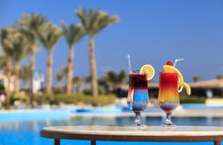 Two cocktails by the pool. On a background of palms and blue sky Stock Photography