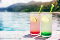 Two cocktails, red and green, at pool side Royalty Free Stock Photography