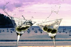 Two cocktails with splashing martini and olives on a sunset beach royalty free stock images