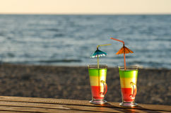 Two cocktails with straws on a wooden table top in the sun on the beach, empty space Royalty Free Stock Photos