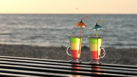 Two cocktails with straws on a wooden tabletop into the sunset on the beach, the sea in the background stock video footage