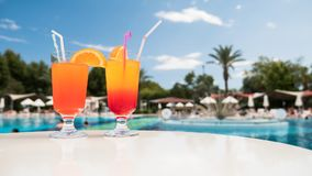 Two cocktails are on the table against the background of the pool. Holiday at the resort with swimming pool.  royalty free stock image