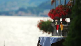 Two cocktails on the table in the summer cafe. Lake Como, Italy on background stock video