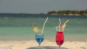 Two cocktails on the table at tropical beach. Blue and pink beverages stock video footage