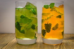 Two cocktails yellow and green with ice and mint. Two cocktails with ice and mint Stock Photos