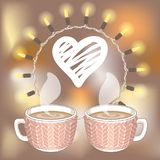 Two cocoa or coffee cups and white hatching heart. Two cocoa or coffee cups with knit cover and white hatching heart on blurred background. Round lights garland Royalty Free Stock Images