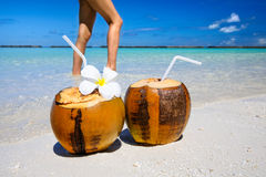 Two coconut cocktails on white sand beach with woman slim sexy legs next to clean sea water. Vacation and travel concept Stock Photos