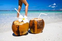 Two coconut cocktails on white sand beach with woman slim sexy legs next. Vacation and travel concept Royalty Free Stock Photos