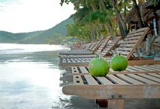 Two coconut drinks on the beach chair Royalty Free Stock Image