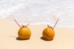 Two coconuts with drinking straw on a sandy tropical beach. Sea in the background . Summer vacation concept Stock Photo