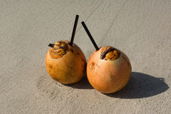 Two coconuts with drinking straws on a beach Stock Photo
