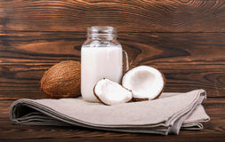 Two coconuts and a mason jar with fresh milk on a gray bag and on a wooden background. Exotic and tropical fruits. A beautiful composition of a mason jar with Royalty Free Stock Photography
