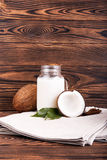Two coconuts and a mason jar with fresh milk on a gray bag and on a wooden background. Exotic and tropical fruits. A beautiful composition of a mason jar with Stock Photos