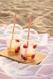 Two coctails in sand, sunset time Royalty Free Stock Photography