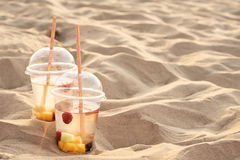 Two coctails in sand, sunset time Royalty Free Stock Images