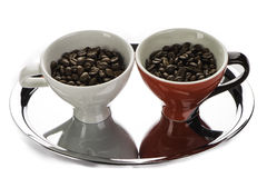 Two coffe cups with beans. One red and other white on the metal tray Stock Photo