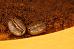 Two coffee beans and ground coffee Stock Photos