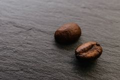 Two coffee beans on a rough surface. Close up, side view Stock Image