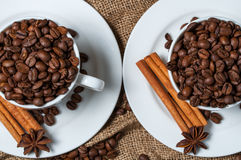 Two coffee cups with coffee beans, aniseed and cinnamon. Royalty Free Stock Photo