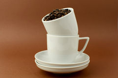 Two coffee cups with coffee beans brown background.  Stock Image