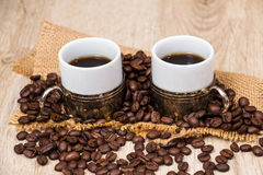 Two coffee cups with coffee beans Stock Images