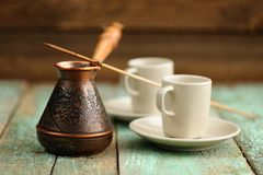 Two coffee cups and copper cezve with fresh black coffee on old Stock Images