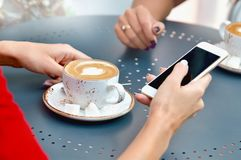 Two coffee cups and hands of young women with smartphone at outdoor cafe Stock Photo