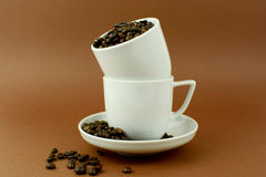 Two coffee cups with lot of coffee beans brown background.  Stock Photography