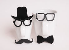 Two coffee cups in mans image. Hipster style, glasses, mustache, hat, bow tie Stock Photo