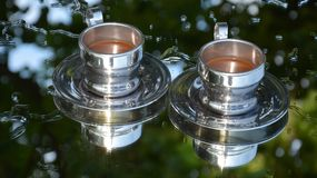 Two coffee cups mirror image Royalty Free Stock Photos